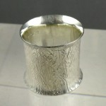 Hammer textured sterling ring with flared edges.
