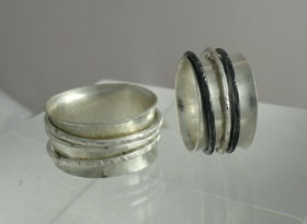 Student project. Sterling anticlastic rings with moving bands.