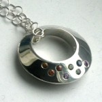 Hollow sterling pendant flush set with sapphires
